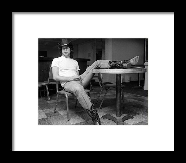 John Travolta Framed Print featuring the photograph John Travolta, With His Hat And Boots by New York Daily News Archive