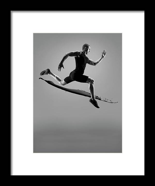 People Framed Print featuring the photograph Male Athlete Running Above Liquid Splash by Jonathan Knowles