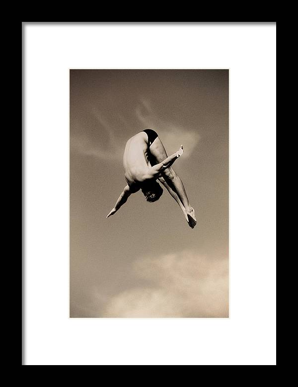 Diving Into Water Framed Print featuring the photograph Male Diver In Mid-air by David Madison