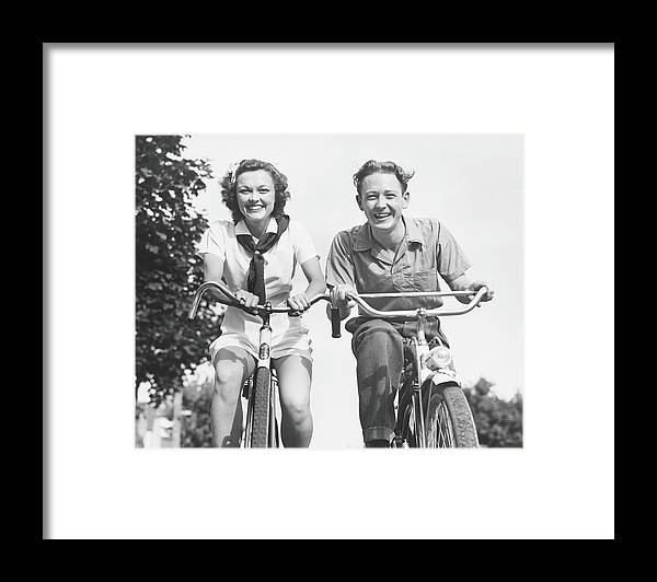 Young Men Framed Print featuring the photograph Man And Woman Riding Bikes, B&w, Low by George Marks
