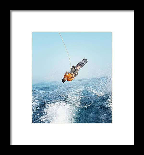 One Man Only Framed Print featuring the photograph Man Performing Wakeboarding Stunt At Sea by Paul Bradbury
