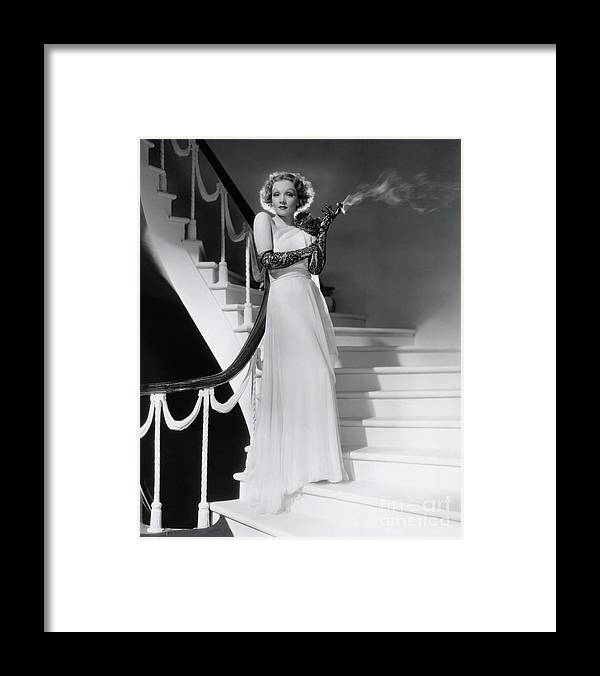 Smoking Framed Print featuring the photograph Marlene Dietrich Smoking On Staircase by Bettmann
