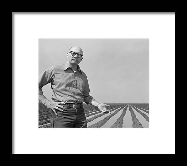 Mature Adult Framed Print featuring the photograph Mature Man Gesturing At Ploughed Field by Tom Kelley Archive