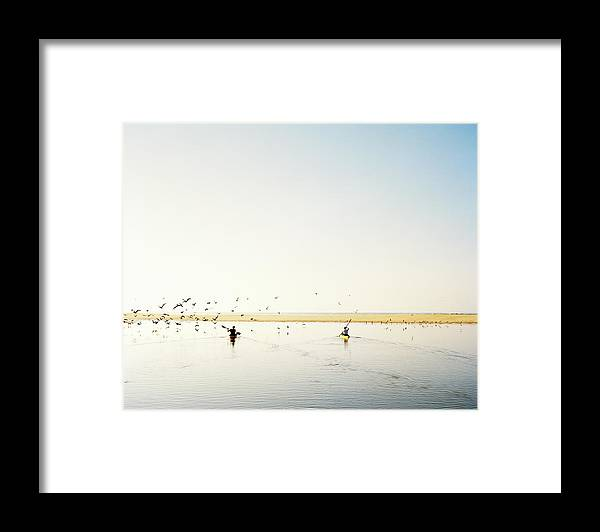 People Framed Print featuring the photograph Men Paddling Kayaks To The Beach by Julien Capmeil