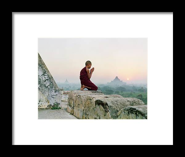 Child Framed Print featuring the photograph Myanmar, Bagan, Buddhist Monk Praying by Martin Puddy