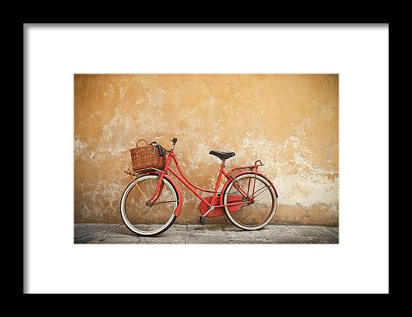 Leaning Framed Print featuring the photograph Old Red Bike Against A Yellow Wall In by Romaoslo