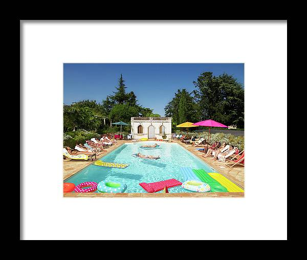 Young Men Framed Print featuring the photograph People Enjoying Summer Around The Pool by Ghislain & Marie David De Lossy