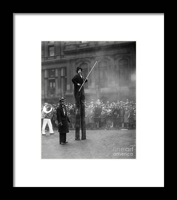 Crowd Of People Framed Print featuring the photograph Performer On Stilts by Bettmann