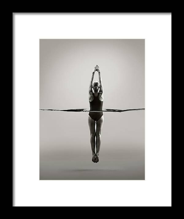 Diving Into Water Framed Print featuring the photograph Rear View Of Female Swimmer by Jonathan Knowles