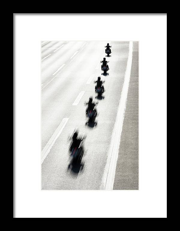 In A Row Framed Print featuring the photograph Rear View Of Row Of Motorcycle Riders by Jorg Greuel
