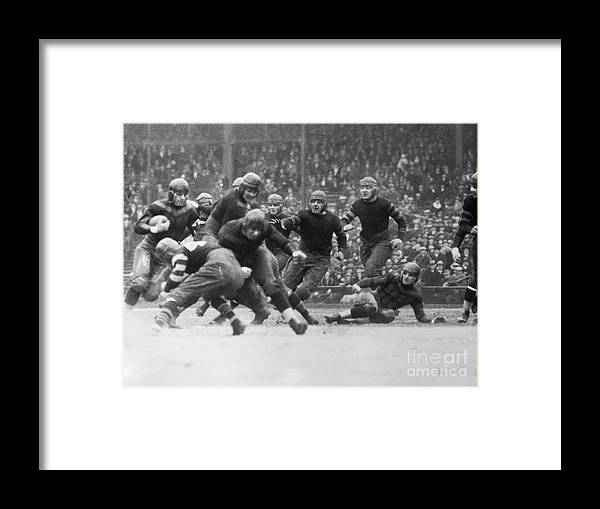 Arizona Cardinals Framed Print featuring the photograph Red Grange Breaking Through A Defensive by Bettmann