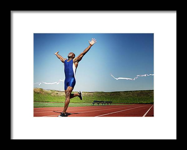 Human Arm Framed Print featuring the photograph Runner Crossing Finish Line by Jupiterimages