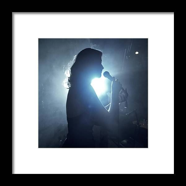 25-29 Years Framed Print featuring the photograph Silhouette Of Woman Using Microphone by Frank Herholdt