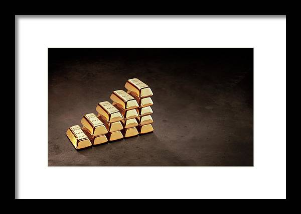 In A Row Framed Print featuring the photograph Stepped Stack Of Gold On Dark Surface by Anthony Bradshaw