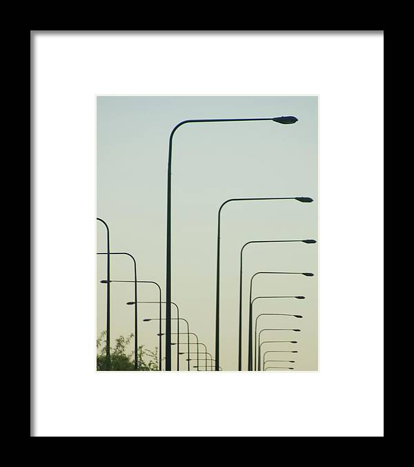 In A Row Framed Print featuring the photograph Streetlights Against Afternoon Sky by By Ken Ilio
