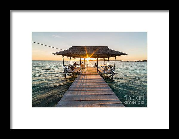 Dusk Framed Print featuring the photograph Tourist Sitting On Wooden Jetty While by Fabio Lamanna