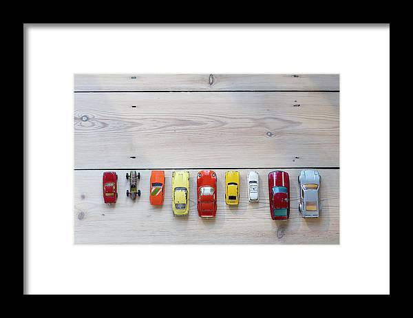 In A Row Framed Print featuring the photograph Toy Cars Lined Up In A Row On Floor by Dougal Waters