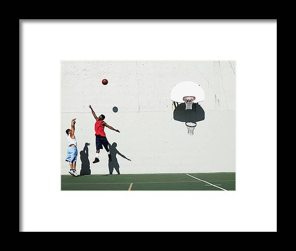 Young Men Framed Print featuring the photograph Two Young Men Playing Basketball by Thomas Barwick