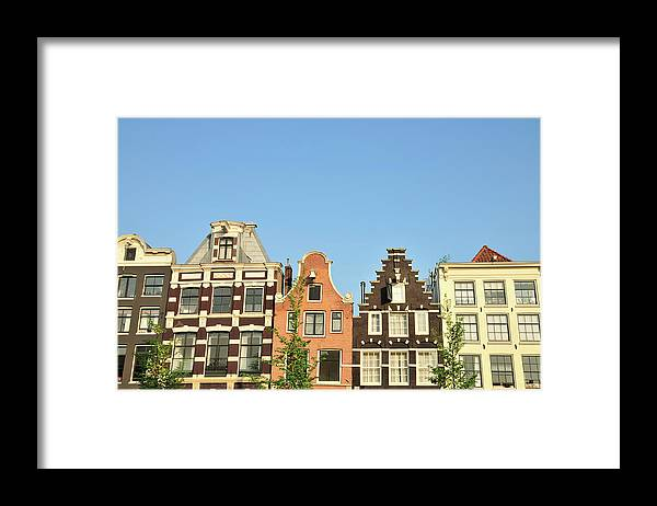 In A Row Framed Print featuring the photograph Typical Canal Houses, Amsterdam, The by Gorazdbertalanic