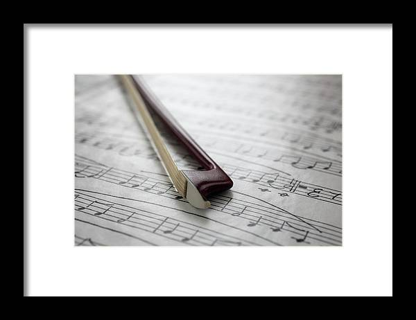 Sheet Music Framed Print featuring the photograph Violin Bow On Music Sheet by Daniel Allan