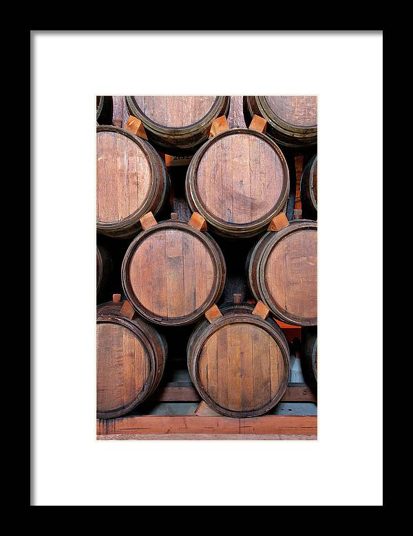 Fermenting Framed Print featuring the photograph Wine Barrels Stacked Inside Winery by Yinyang