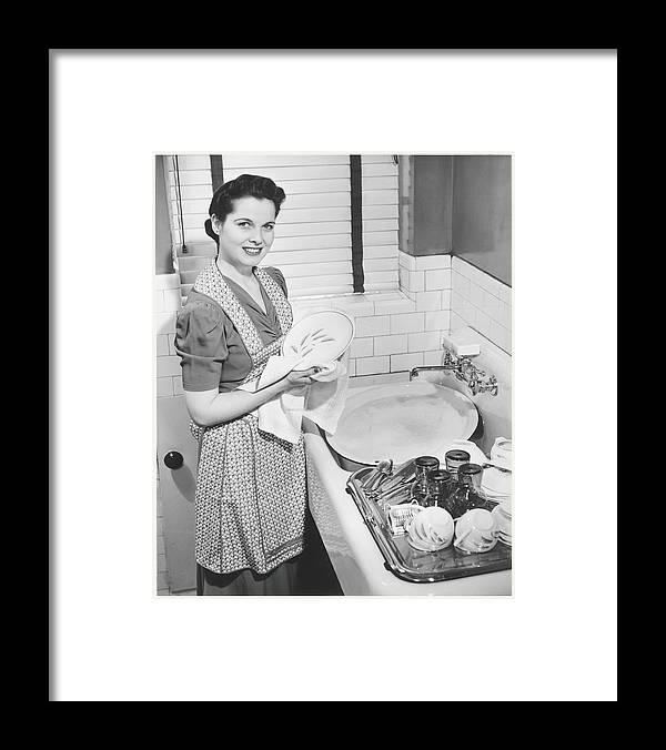 Three Quarter Length Framed Print featuring the photograph Woman Drying Dishes At Kitchen Sink by George Marks