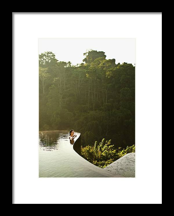 Tropical Rainforest Framed Print featuring the photograph Woman In Infinity Pool At Sunrise. Bali by Matthew Wakem