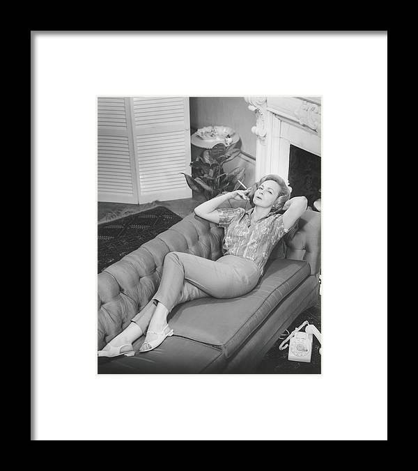 Smoking Framed Print featuring the photograph Woman Relaxing On Sofa, B&w, Elevated by George Marks