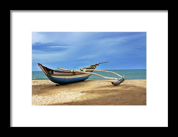 Tranquility Framed Print featuring the photograph Wooden Catamaran By The Sea Shore by Juavenita Alphonsus