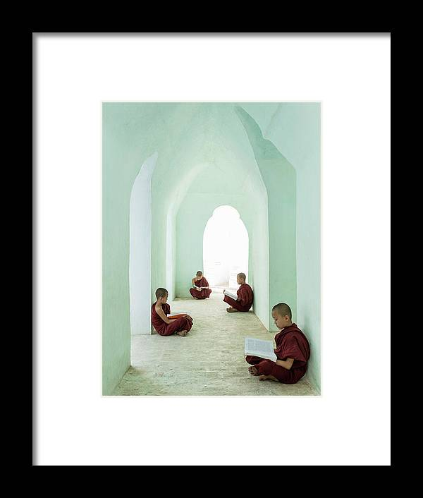 Arch Framed Print featuring the photograph Young Buddhist Monks Reading In Temple by Martin Puddy
