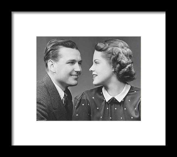 Young Men Framed Print featuring the photograph Young Couple Looking In Eyes In Studio by George Marks