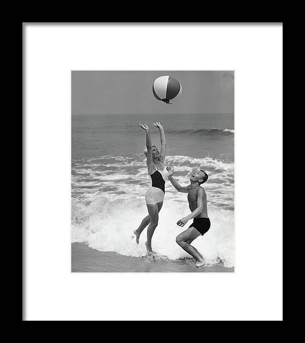 Young Men Framed Print featuring the photograph Young Couple Playing With Beach Ball At by Stockbyte