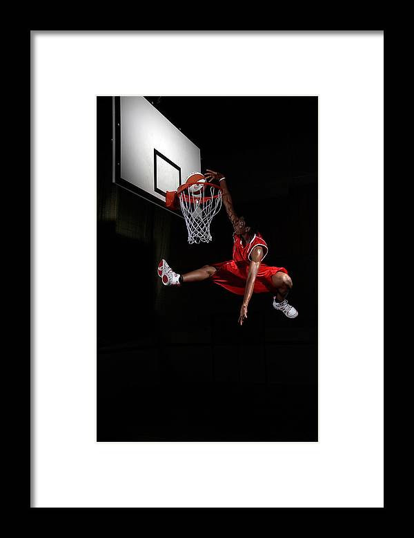 Human Arm Framed Print featuring the photograph Young Man Making A Fancy Dunk by Compassionate Eye Foundation/steve Coleman/ojo Images Ltd