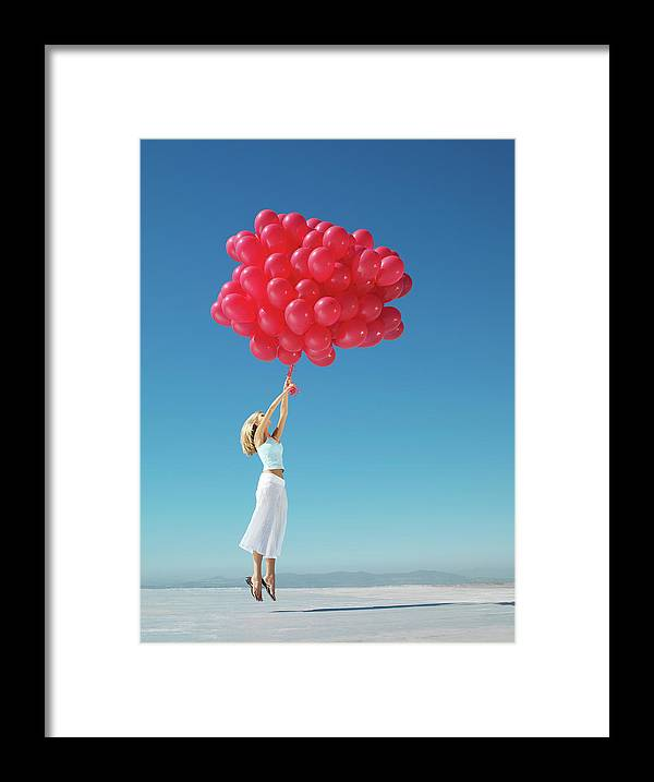 Hand Raised Framed Print featuring the photograph Young Woman Holding On To Large Bunch by Nick Dolding