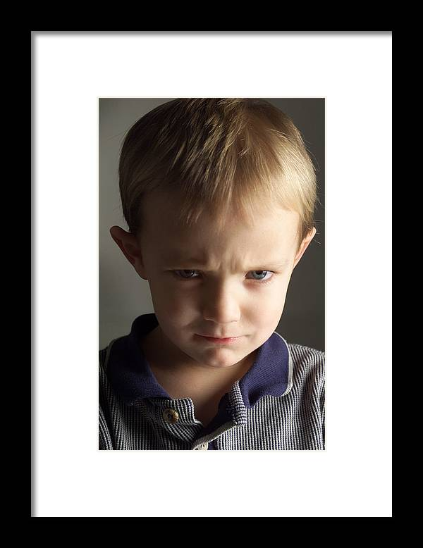 Toddler Framed Print featuring the photograph A Cute Little Caucasian Boy With Light Brown Hair Is Wearing A Stripped Blue Shirt And Pouting by Photodisc