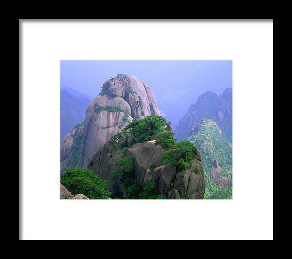 Part Of A Series Framed Print featuring the photograph A Rocky Outcropping Overlooks A Mist-covered China Mountain Range by Rubberball