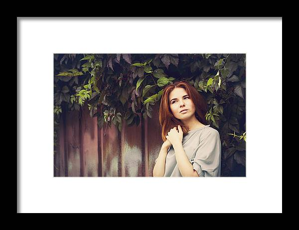 People Framed Print featuring the photograph Caucasian woman standing under leaves by fence by Maxim Chuvashov
