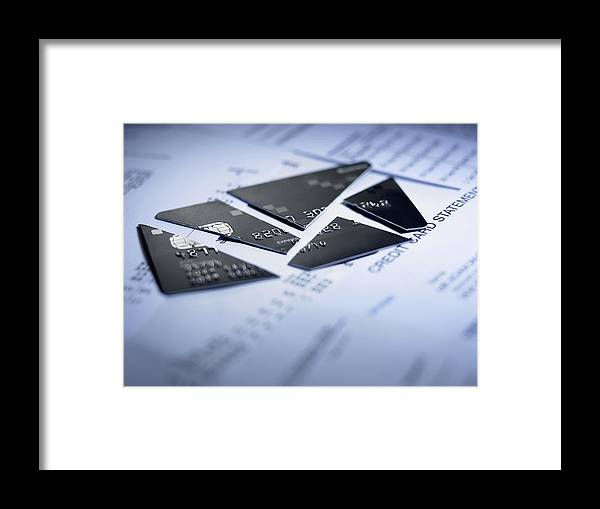 Debt Framed Print featuring the photograph Close up of cut pieces of credit card by Adam Gault