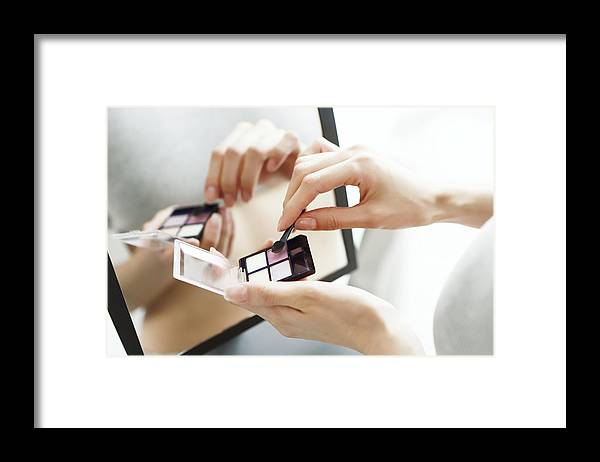 Eyelash Framed Print featuring the photograph Close up of woman holding eye shadow pallet by Runstudio