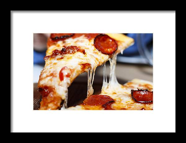 Pepperoni Pizza Framed Print featuring the photograph Closeup of a piece of pepperoni pizza. Italian pizza. by Gannamartysheva