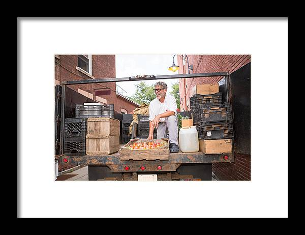 Working Framed Print featuring the photograph Farmer unloading crates of organic tomatoes outside grocery store by Heshphoto
