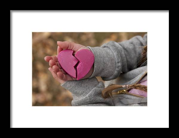 Child Framed Print featuring the photograph Girl holding broken heart by Design Pics/Ron Nickel
