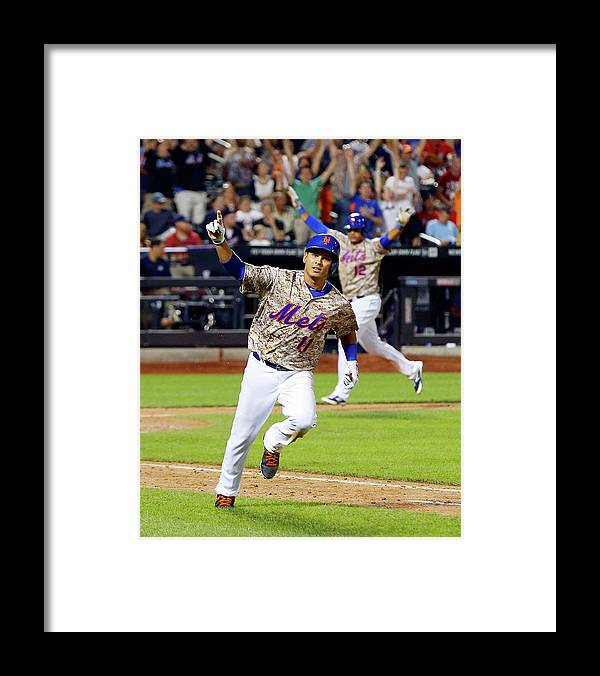 Scoring Framed Print featuring the photograph Juan Lagares And Ruben Tejada by Jim Mcisaac