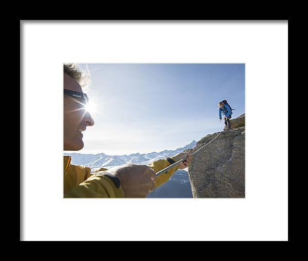 Young Men Framed Print featuring the photograph Mountaineer pulls rope tight to teammate, mtns by Ascent Xmedia