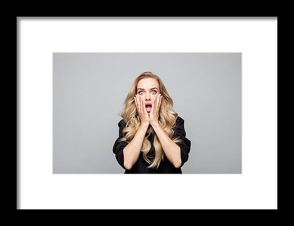 Disbelief Framed Print featuring the photograph Portrait of shocked young woman with hands on face by Izusek