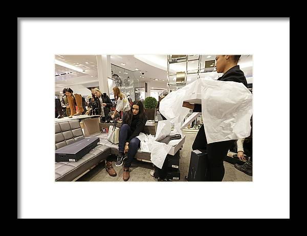 Working Framed Print featuring the photograph Shoppers Inside Macy's Inc. And Toys R Us Inc. Stores Ahead Of Black Friday Sales by Bloomberg