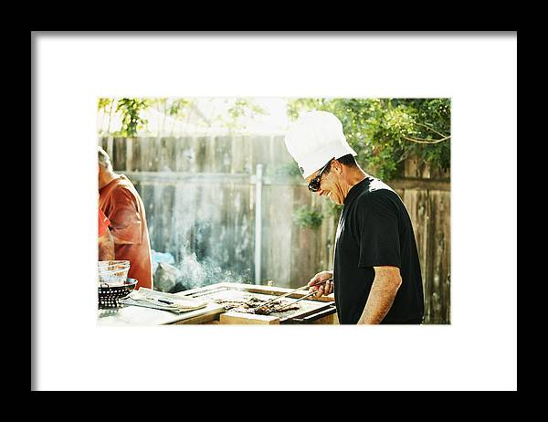 Expertise Framed Print featuring the photograph Smiling father grilling in backyard during family barbecue by Thomas Barwick