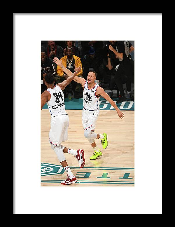 Nba Pro Basketball Framed Print featuring the photograph Stephen Curry and Giannis Antetokounmpo by Garrett Ellwood