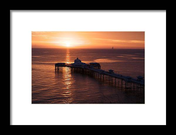 Piers Framed Print featuring the photograph Sunrise over Llandudno pier 2 by Christopher Rowlands