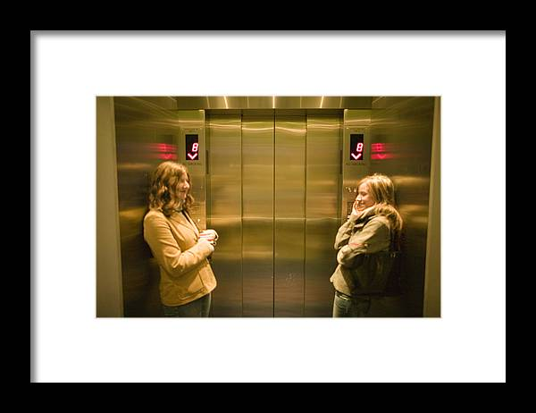 Three Quarter Length Framed Print featuring the photograph Two young women waiting in elevator by Photodisc